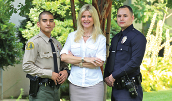 Alise Cayen (center), the coordinator of the Reseda High School's Police Academy Magnet School with two distinguished graduates - Hector Logos, a Los Angeles County Deputy Sheriff and Cesar Corrales, one of the first graduates who today serves with the LAPD.