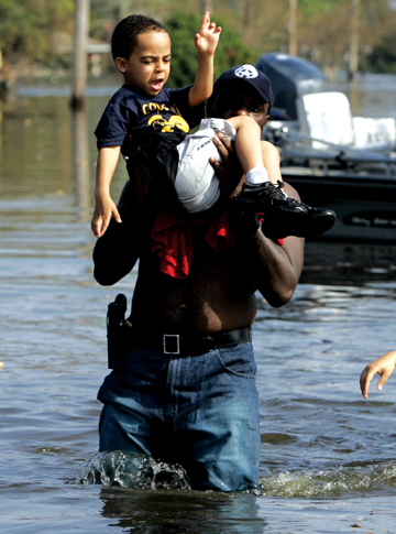 New Orleans Officer carries a child to higher ground in the aftermath of Katrina.