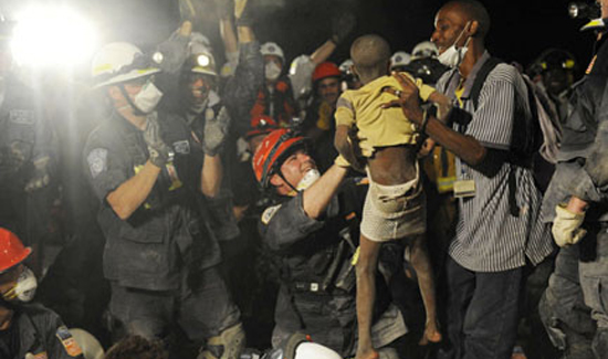 Following the devastating earthquake in Haiti in January 2010, Rich holds up seven-year-old Kiki following five hours of removing debris and tunneling underground with his FEMA Team, New York Task Force One.