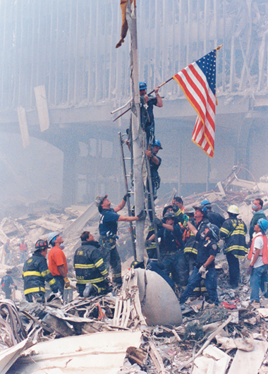 "Rich Miller raises the first American flag at Ground Zero the day following the terrorist attacks. Richie Hartigan, also assigned to the NYPD's Emergency Service Unit, is right below Rich on the ladder. The only sound that could be heard was an FDNY Battalion Chief yelling, ""Present Arms,"" as Rich secured the flag on to the antenna, which had fallen from the top of the Trade Center's North Tower. (Photo courtesy Bill McNulty, NYPD/TARU (Ret))"