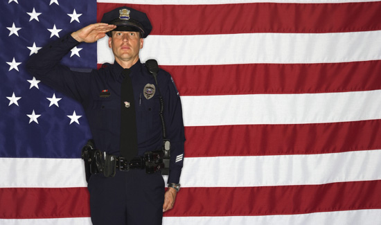 Police officer saluting and American flag