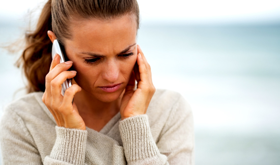 concerned young woman talking cell phone on cold beach