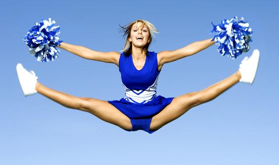 Cheerleader With Pompoms Doing Splits Against Sky