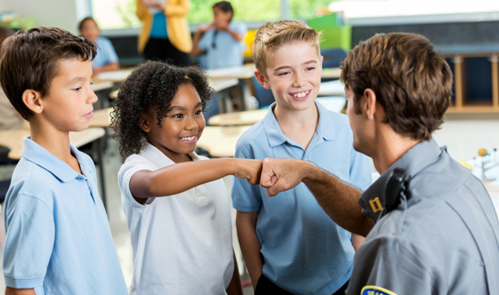 African American student gives policeman a fist bump at school